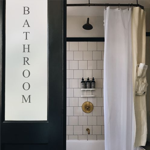 Frosted glass bathroom door with text.