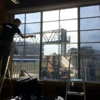 Purlfrost window film installer applying reflective window film to Altitude Real Estate office windows.