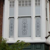 Self-adhesive etch effect window film applied to Victorian era bay window.