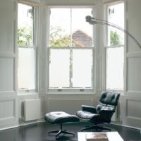 Privacy window film on living room windows with Charles Eames chair in front.