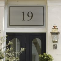 Frosted house number sticker with number 19 applied to transom on Victorian property entrance.