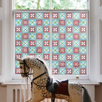Victorian stained glass patterned window film on period window in front of vintage rocking horse.